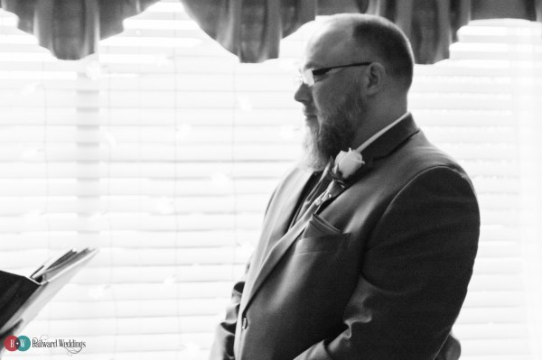 Groom looking at bride in black and white