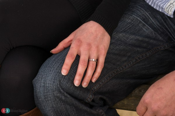 Hand with engagement ring on finger resting on leg
