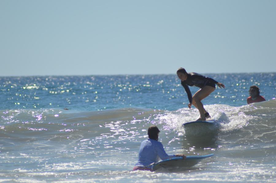 Woman surfing a wave in Baja with her surf instructor behind her