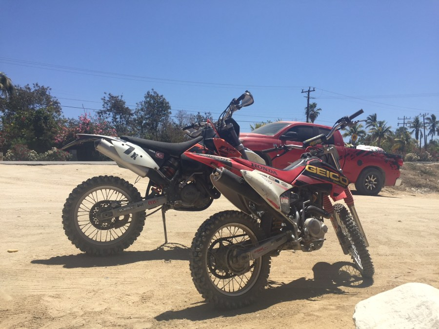 two dirt bikes in a parking lot