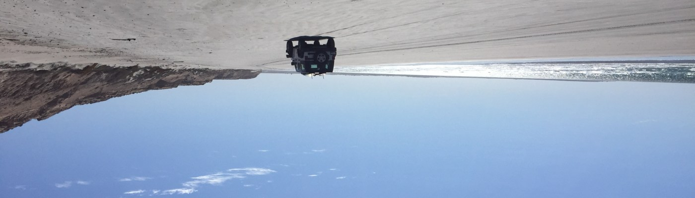 Lone Jeep on a secluded beach