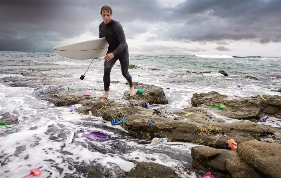 surfer navigates rocks and plastic