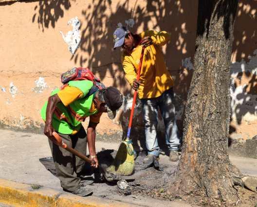 Miembros de la brigada municipa limpiando calle de La Sabana