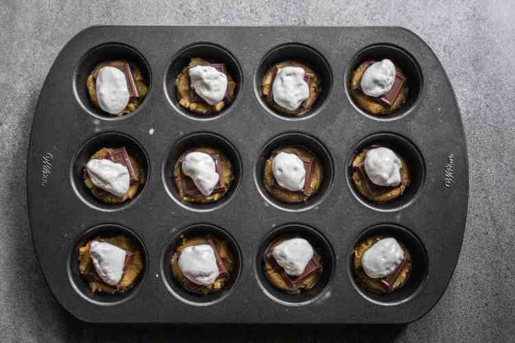 muffin tin with marshmallow topping on top of chocolate of the s'mores cookie cups