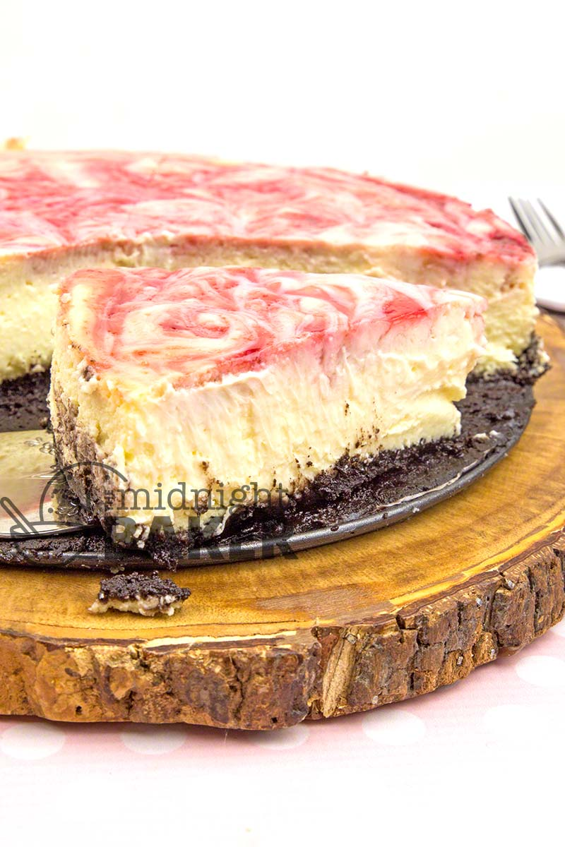 Cheesecake topped with a tart raspberry swirl on top of a decadent chocolate crust.