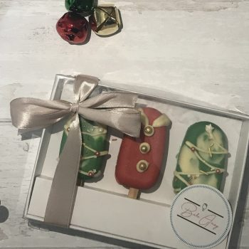 A box of three christmas cakesicles on a white wooden background with christmas wreath and decorations around the edge