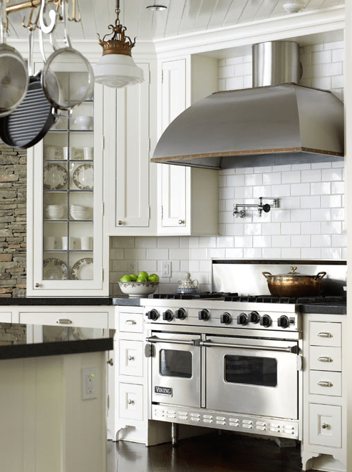 kitchens - stainless steel range hood pot filler beadboard ceiling ivory kitchen cabinets ivory beadboard kitchen island white subway tiles backsplash brick wall Absolute Black granite countertops copper pot rack