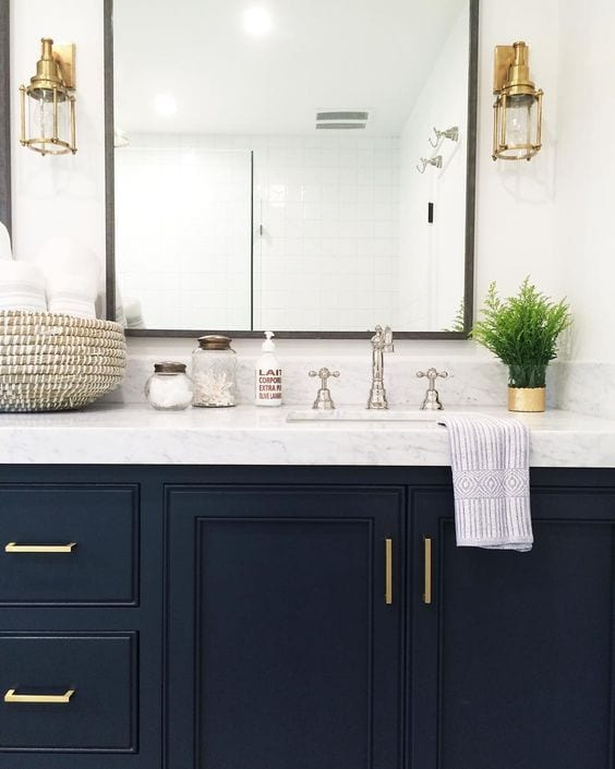 Photo Credit: Chris Loves Julie Blog. The natural iron mirror frames work ad a mediator between the gold statement sconces, silver sink faucets, and soft gold cabinet handles.