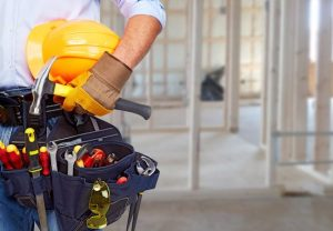 Man holding hard hat and wearing tool belt