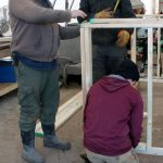 Mark, Joe, and Sam consulting on the chicken brooder construction.