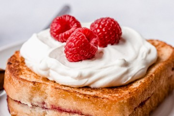 one stack of raspberry stuffed french toast with whipped cream and fresh raspberries