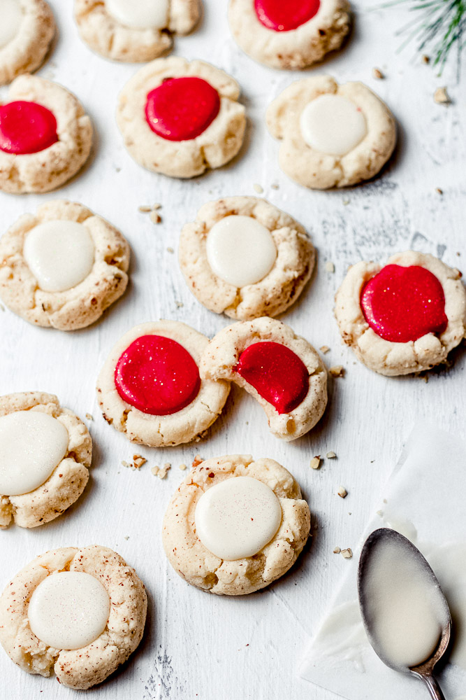 close up of bitten cookie with other red and white thumbprint cookies