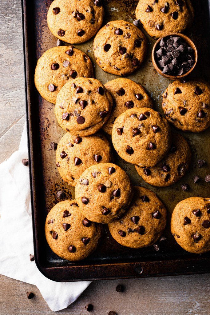pumpkin chocolate chip cookies on a brown tray with a brown back drop and extra chocolate chips
