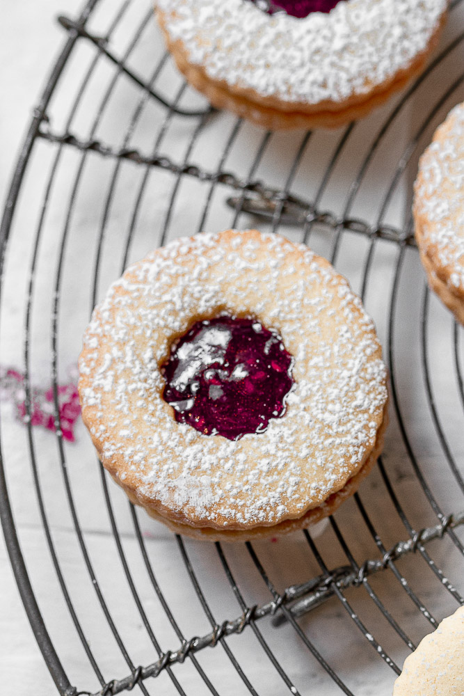 close up of sandwich cookie filled with raspberry jam