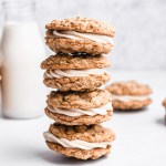 stack of oatmeal cream pies with a glass of milk
