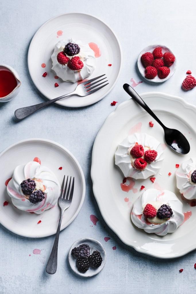 flatlay of mini lemon pavlovas with raspberries and blackberries