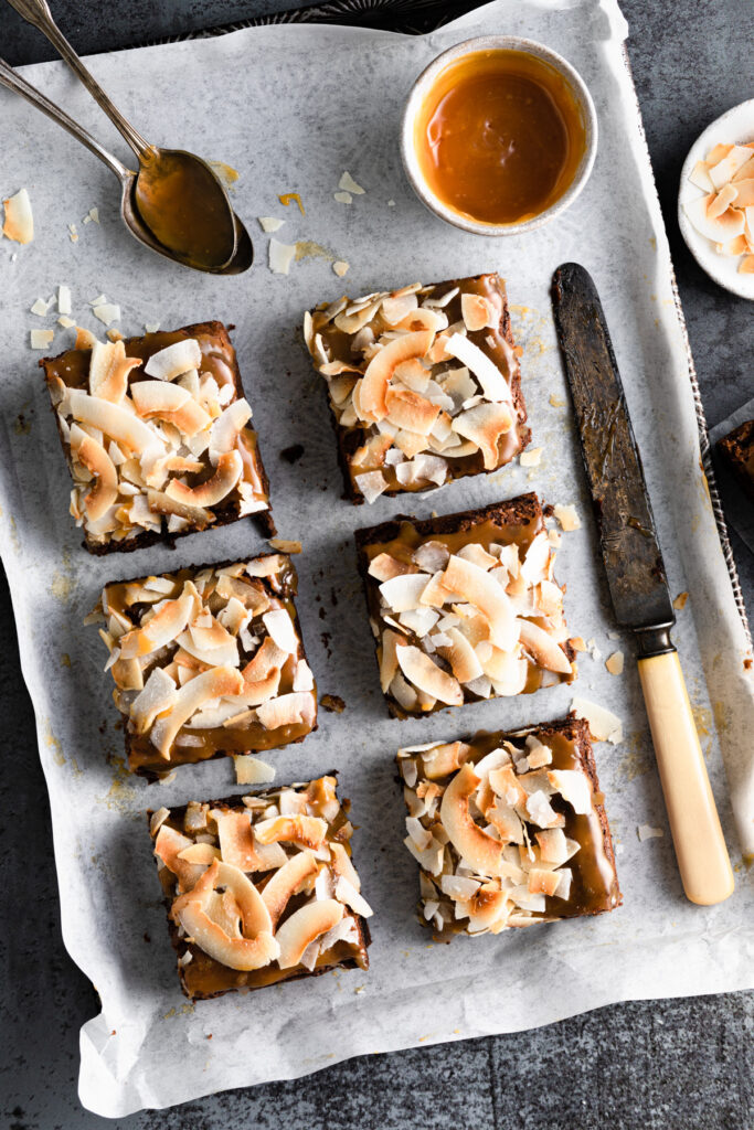 cut up squares of coconut caramel brownies on a tray