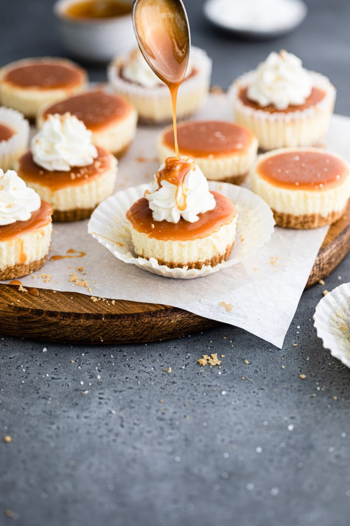 caramel being drizzled onto mini cheesecakes