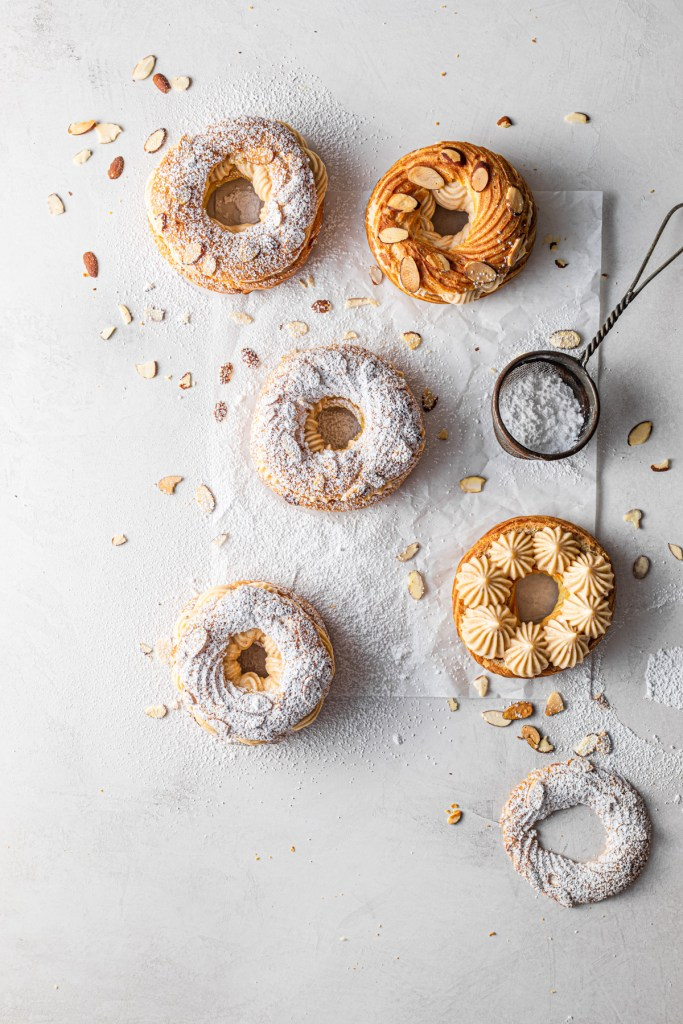 flatlay of mini paris brests with almonds, powdered sugar, and almond pastry cream