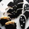 Halloween royal icing cookies with bat cookies, cauldron cookies, ghost cookies, and coffin cookies