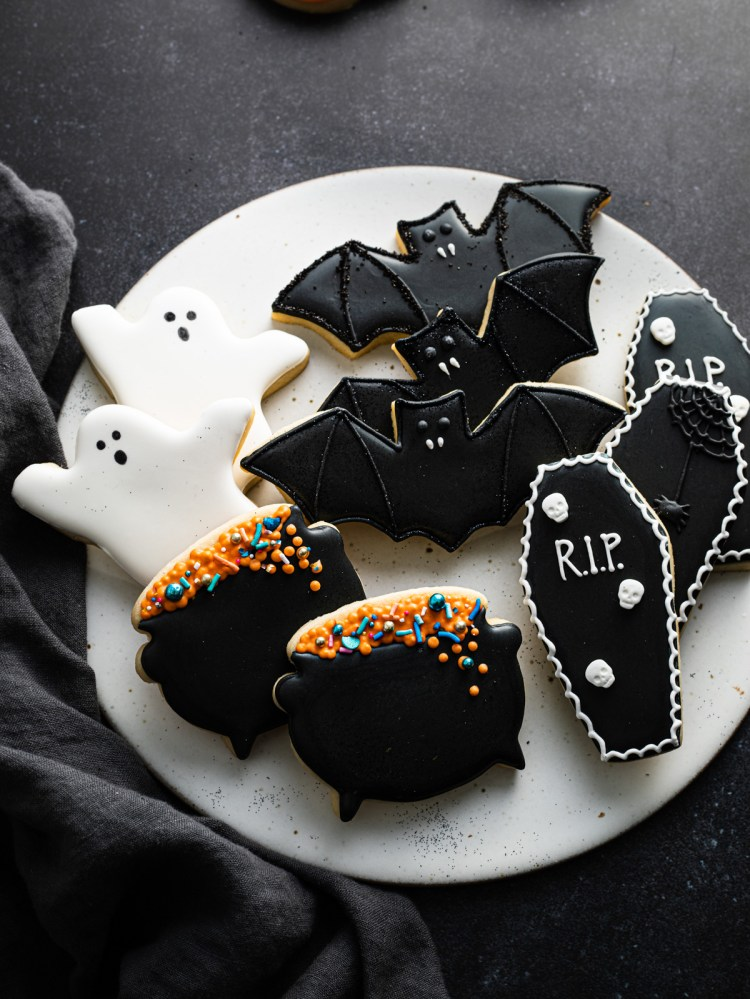Halloween royal icing cookies including ghost cookies, cauldron cookies, bat cookies, and coffin cookies
