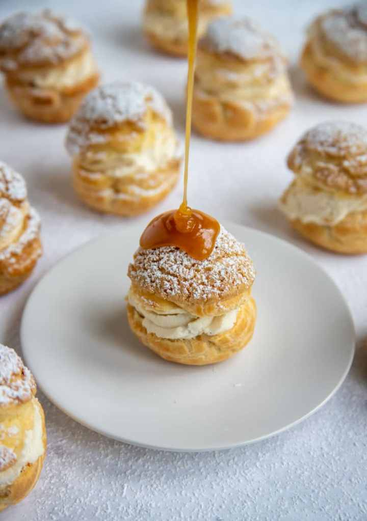 Apple Filled Cream Puff on a white plate drizzled with apple cider caramel sauce