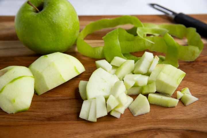 Granny Smith apples on a cutting board.  One apple is chopped, the other is whole