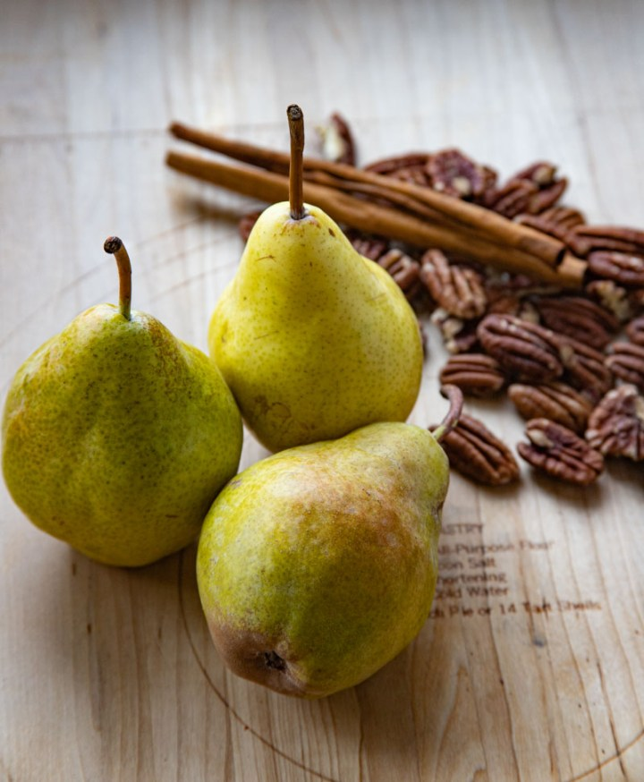 Whole Pears, Pecans and Cinnamon Sticks arranged on a wooden board