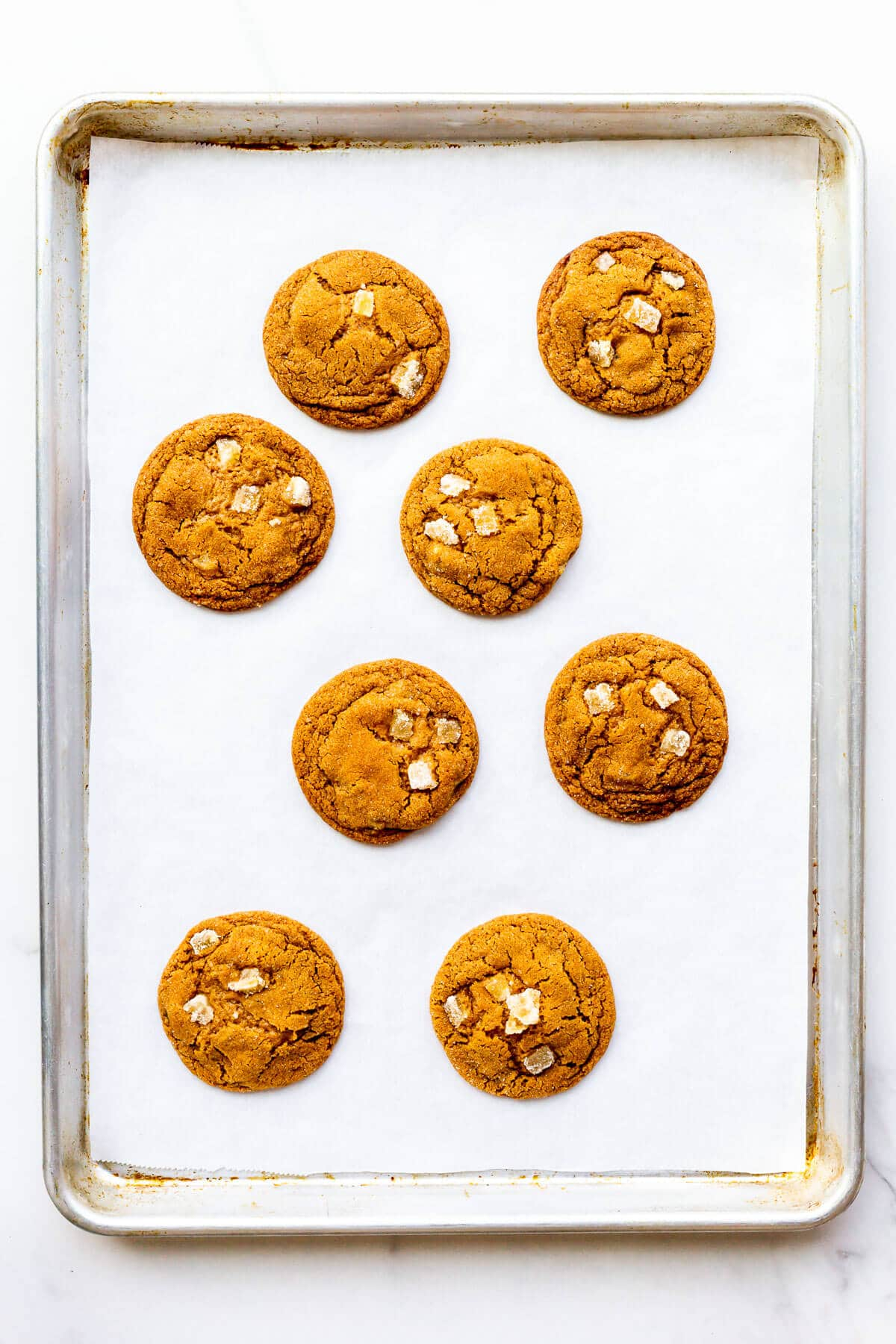 Freshly baked ginger cookies cooling slightly on a sheet pan to firm them up before transferring to a cooling rack.