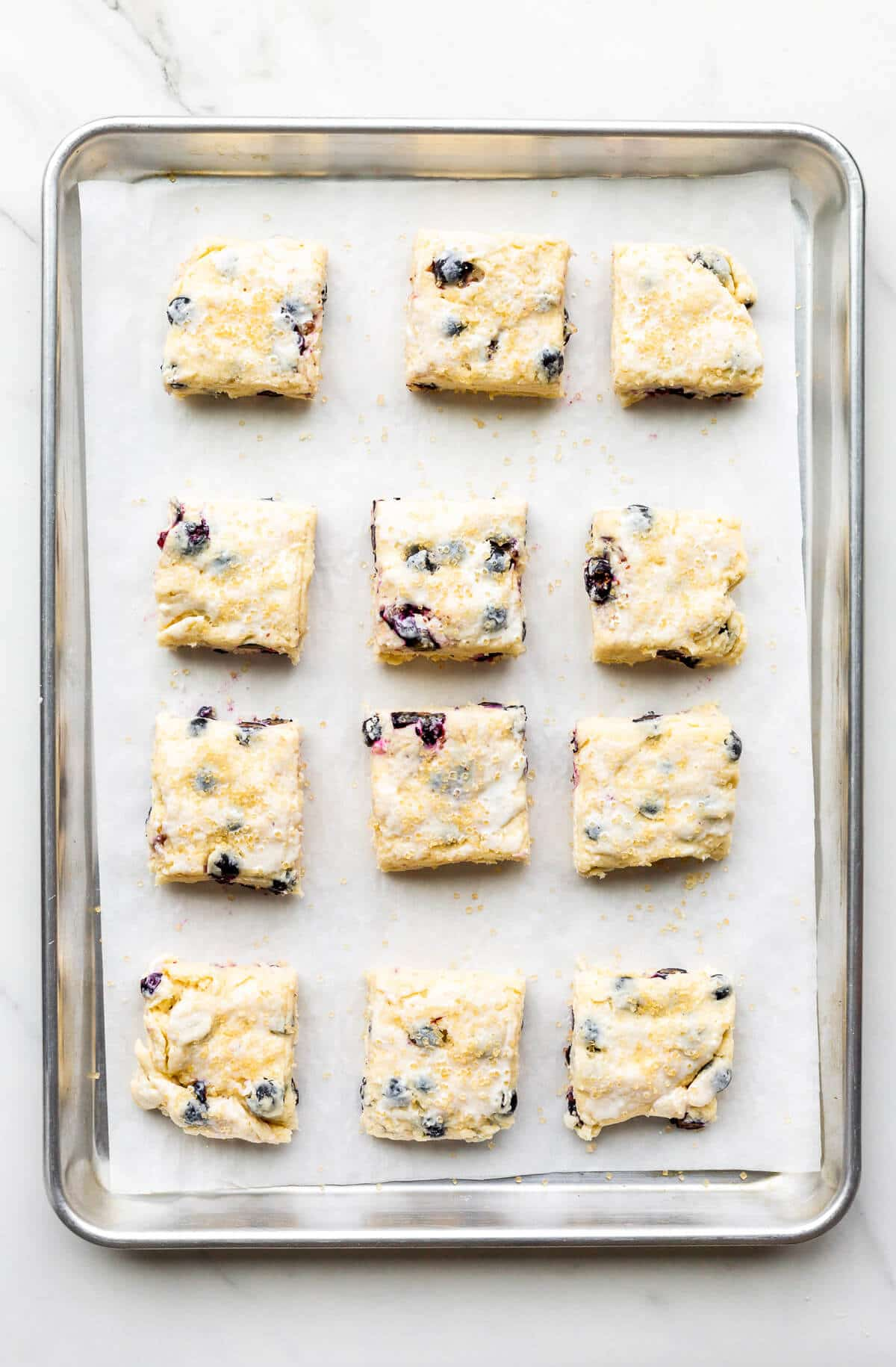 A sheet pan with scones with fresh blueberries before baking.
