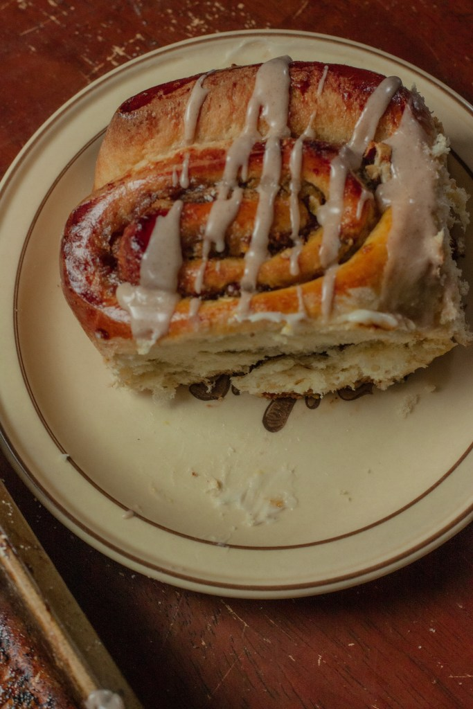 A plate with a sweet roll on it and lots of cinnamon drizzle.