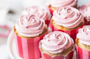 Strawberry cupcakes with strawberry buttercream, in pink, red, and white cupcake papers, sitting on a white cake stand. The buttercream has been piped in the shape of a rosette, and there is a pink-trimmed cloth in the background.