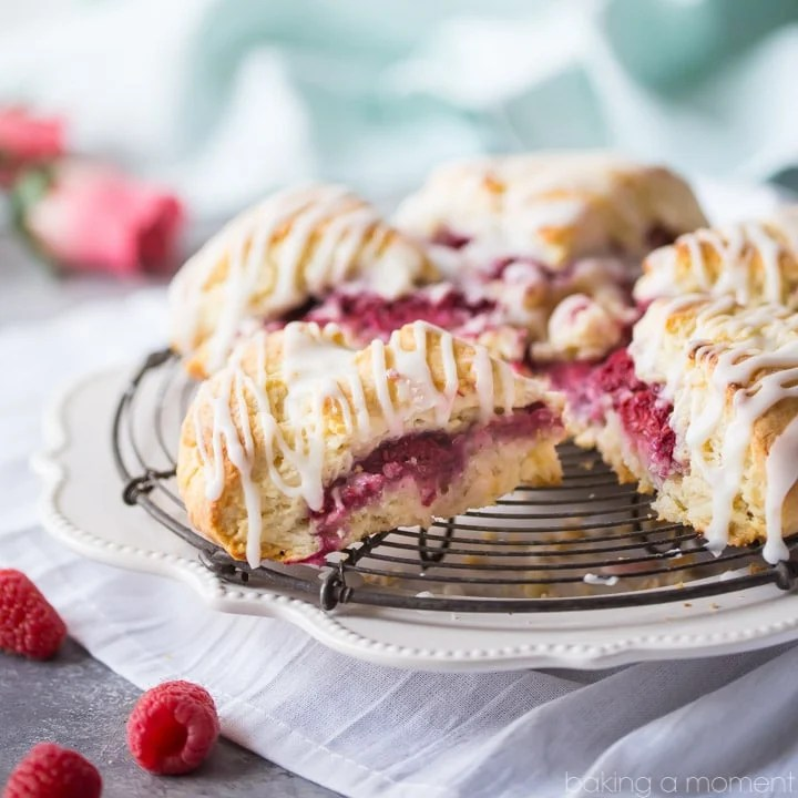 Raspberry Cream Scones with Rosewater Glaze: a fresh batch of scones, filled with raspberries and drizzled with glaze.