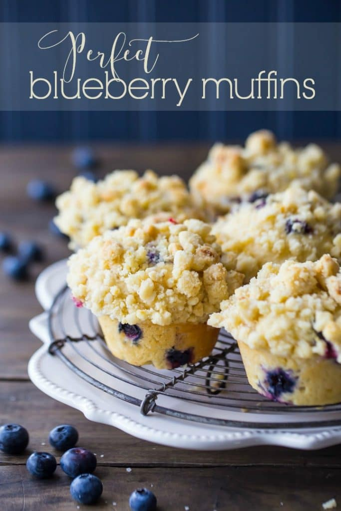 Vertical Image of bakery-style blueberry muffins on a cooling rack with text overlay.