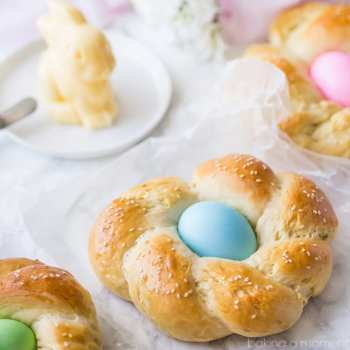 Easter Egg Bread: a golden brown braided loaf with a pastel-colored egg nestled in the middle.