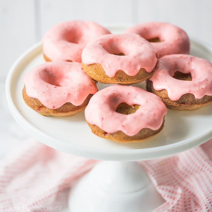 Baked strawberry donuts with pink strawberry icing, on a white cake stand.