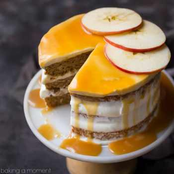 Triple-layer apple honey cake on a cake stand, with cream cheese frosting and honey caramel drizzle, garnished with fresh apple slices.