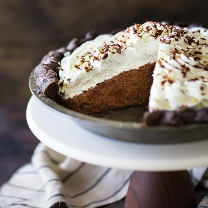 Chocolate Cream Pie with chocolate crust, whipped cream, and chocolate shavings. A slice is taken out of the pie so the fluffy chocolate mousse filling is visible.