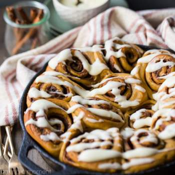 Cast iron skillet with gingerbread cinnamon rolls, drizzled with cream cheese icing. Cinnamon sticks and gold forks in the background.