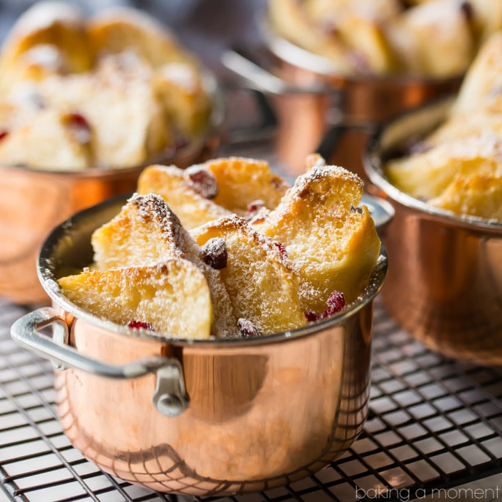 Individual bread & butter puddings, in mini copper pots, with toasty buttered bread, dried cranberries, and powdered sugar, on a wire cooling rack.