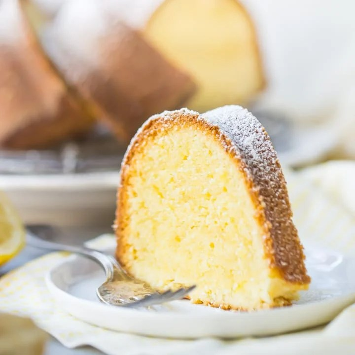 A tall slice of buttery lemon pound cake on a white plate over a yellow napkin, with a silver fork alongside.