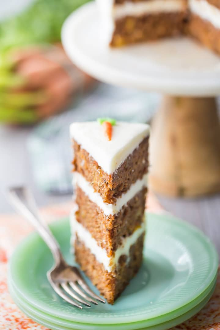 Tall slice of triple-layer carrot cake with cream cheese frosting, on a green plate with an orange napkin below.