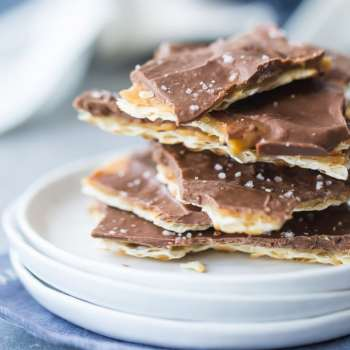 Square image of a stack of matzo toffee on a small white plate, with a blue napkin underneath.