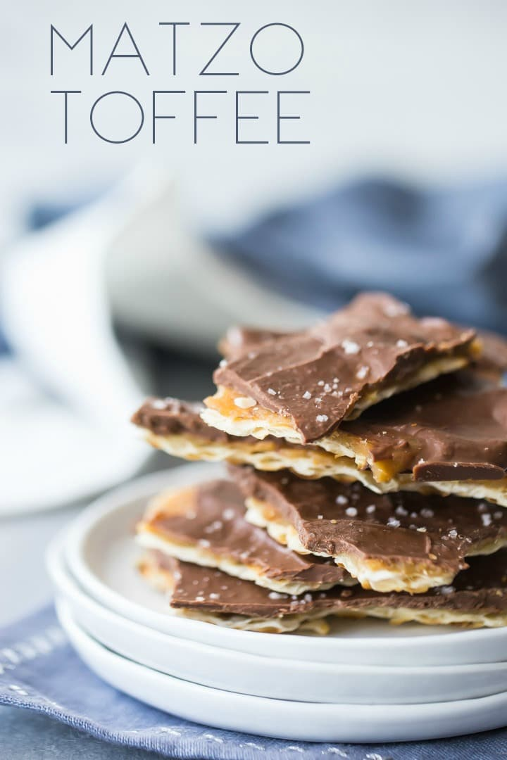 Small white plates on a blue napkin, piled with a stack of matzo toffee, with a text overlay.