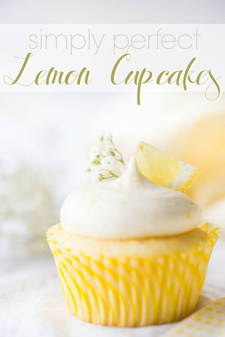 Text overlayed image of a lemon cupcake with lemon curd filling & lemon cream cheese frosting, garnished with baby's breath and a wedge of fresh lemon.