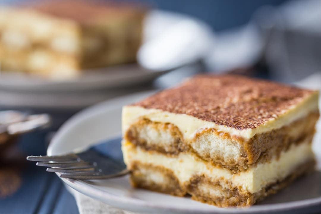 Horizontal image of a slice of tiramisu on a white plate with a blue background.