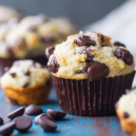 Square image of a freshly baked chocolate chip muffin on an aqua-painted wood background, with chocolate chip mini-muffins in the background.