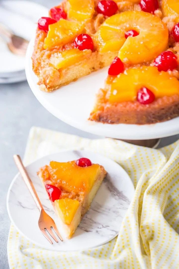 Vertical image of a pineapple upside down cake on a stand with a slice cut out and plated.