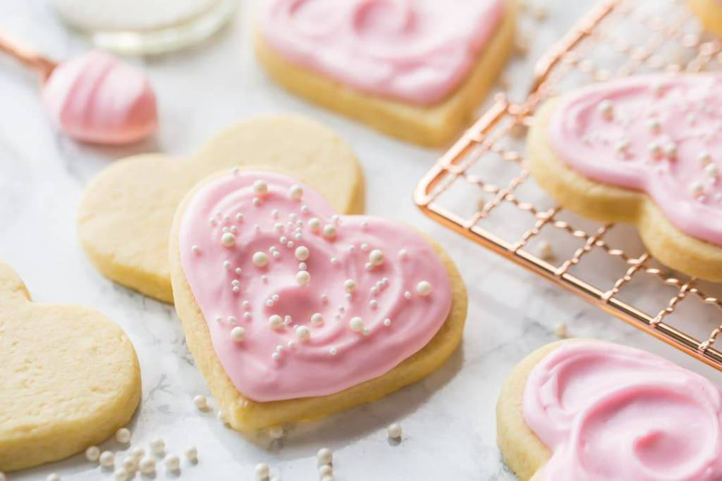 Horizontal image of heart-shaped soft sugar cookies with pink sugar cookie icing and sprinkles.