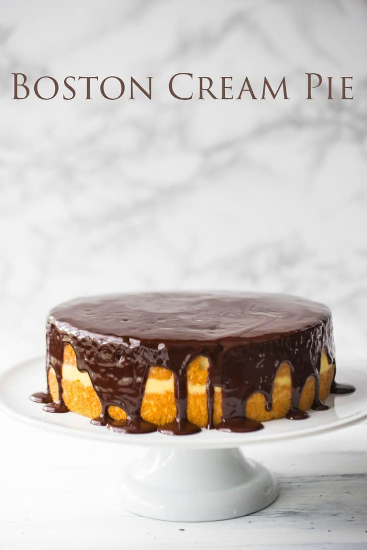 Traditional Boston Cream Pie on a cake stand with sponge cake, vanilla pudding, and dark chocolate icing.